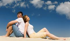 Portrait of relaxing couple sitting back to back on sandy beach against blue sky Stock Photos