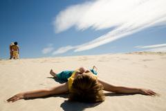 image of restful boy lying on sand under blue sky and enjoying sunny day - stock photo