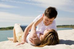 Image of amorous couple lying on sandy beach and embracing at each other Stock Photos
