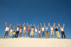 Image of many friends standing on sandy beach with their arms raised against blu Stock Photos