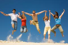 photo of excited people jumping on sandy beach with their arms raised against bl - stock photo