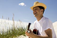 portrait of handsome man playing the guitar and singing something on sunny day - stock photo