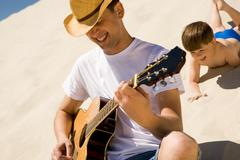 portrait of happy man in cowboy hat playing the guitar with his son at backgroun - stock photo