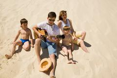 image of cheerful man playing the guitar with his sons and wife near by - stock photo