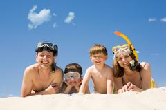 Portrait of diving family lying on sand against blue sky and smiling at camera Stock Photos