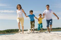 photo of happy parents holding their sons by hands and running down sandy shore - stock photo
