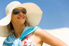 Portrait of pretty young lady in hat looking aside through sunglasses during vac Stock Photos