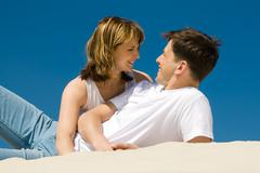 Image of amorous couple lying on sandy beach and looking at each other Stock Photos