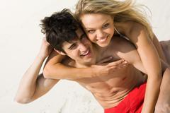 Photo of happy girl embracing handsome lad and both laughing on the beach Stock Photos
