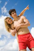 Photo of pretty girl pointing at something with attractive male near by Stock Photos