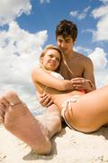 photo of serene girl having rest in her boyfriend's arms while relaxing on sand - stock photo