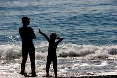 silhouettes of man and child enjoying themselves while sea waves surging onto th - stock photo