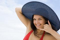 portrait of pretty young lady in hat making gesture by her face and smiling - stock photo