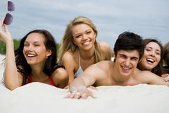 Photo of pretty girls and happy guy lying on sandy beach at leisure Stock Photos