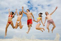 portrait of friends holding by hands and jumping over sandy shore - stock photo