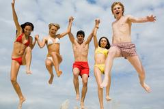 Portrait of friends holding by hands and jumping energetically over sandy shore Stock Photos