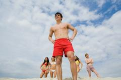 portrait of group of several friends standing on sand with happy guy in front - stock photo