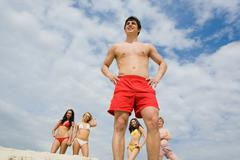 Photo of several friends standing on sand with happy guy in front Stock Photos