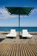 Photo of two deck-chairs with umbrella near by on sandy coast Stock Photos