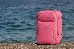 Photo of pink suitcase of a tourist on pebbles with the sea near by Stock Photos