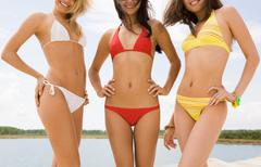 Portrait of three graceful girls in bikini smiling at camera on the beach Stock Photos