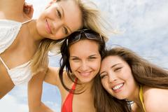 view from below of happy girls in bikini embracing each other and smiling at cam - stock photo