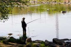 photo of a fisher angling by the river in windless weather - stock photo