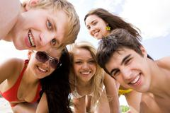 faces of happy girls and guys looking at camera and laughing - stock photo