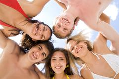 below view of circle of friendly teens looking at camera with blue sky above the - stock photo