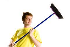 Portrait of man in yellow t-shirt holding brush and looking at camera Stock Photos