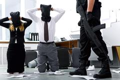photo of kneeling businesspeople wearing black sacks on their heads with burglar - stock photo