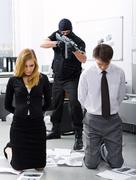 Photo of business co-workers standing on knees being aimed at by evil terrorist Stock Photos