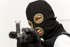 Head of murderer in balaclava pointing his gun at camera and looking into it Stock Photos