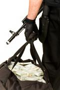 Close-up of bag full of dollar bills being held by gloved hand of robber Stock Photos