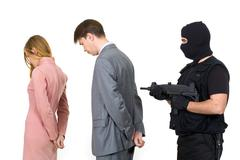 Portrait of two businesspeople standing with terrorist pointing gun at them behi Stock Photos