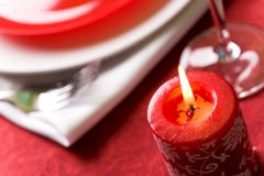 Close-up of red burning candle on festive table Stock Photos