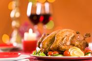 Stock Photo of image of roasted turkey surrounded by vegs on festive table