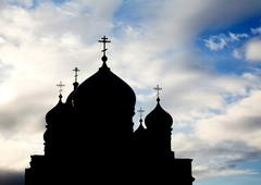 silhouette of several church domes with crosses on tops on background of cloudy - stock photo