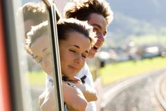 photo of romantic couple looking out of train window while their travel - stock photo