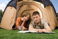 Photo of resting couple lying on green grass in tent and reading guide Stock Photos