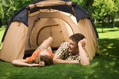 photo of resting couple lying on green grass in tent and enjoying themselves - stock photo