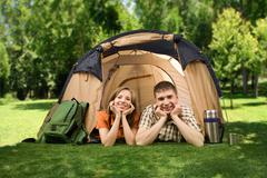photo of cheerful girl and guy lying on green grass in tent and looking at camer - stock photo