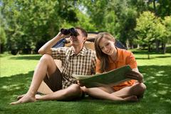 Photo of resting couple sitting on green grass while girl reading paper and guy Stock Photos
