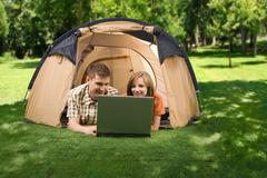 Photo of cheerful girl and guy lying on green grass and looking at laptop monito Stock Photos