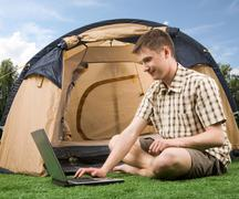 photo of smiling man sitting on green grass and typing with tent near by - stock photo