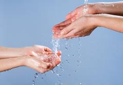 close-up of pair of hands pouring clean water onto palms of another person - stock photo