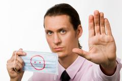 Photo of serious man holding mask and showing palm appealing to stop new virus Stock Photos