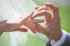 close-up of groom's hand putting wedding ring on bride's finger - stock photo