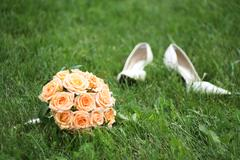 close-up of bridal yellow rose bouquet on background of her white shoes on green - stock photo