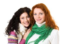 portrait of pretty girls wearing sweaters and scarves and looking at camera with - stock photo